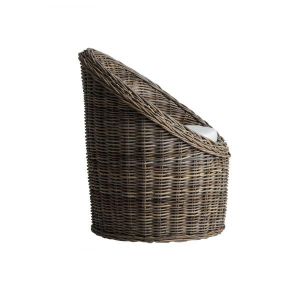 sillón de ratán ovalado. Su acabado marrón y su cojín crudo